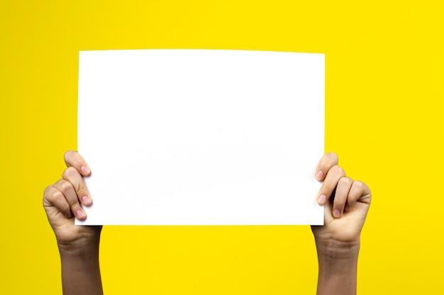 Mains tenant une pancarte d'affiche de carton blanc vierge sur mur jaune