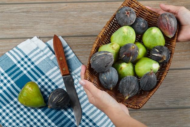 Mains tenant un panier de figues sur table en bois avec un couteau et une nappe.