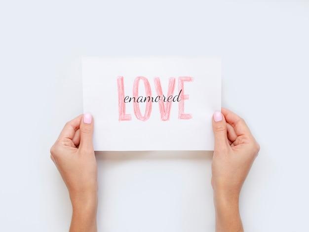 Mains tenant le papier d'amour à plat poser