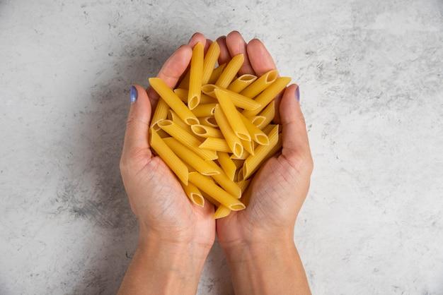 Mains tenant des pâtes penne crues sur une surface blanche.