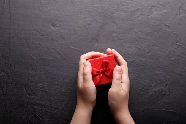 Mains tenant un petit cadeau avec un arc rouge. fermer.