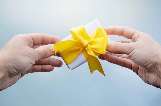 Mains tenant une petite boîte cadeau avec ruban jaune