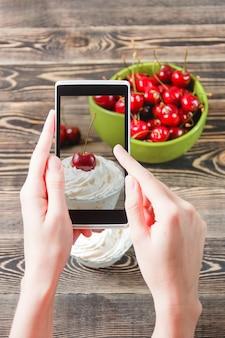 Mains tenant photo cherry jam avec smartphone