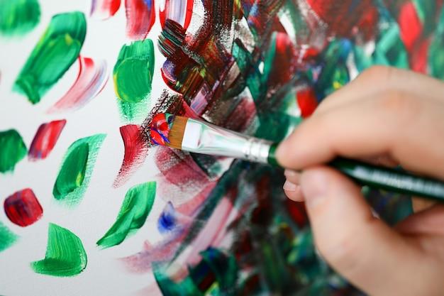 Mains tenant le pinceau avec de la peinture multicolore