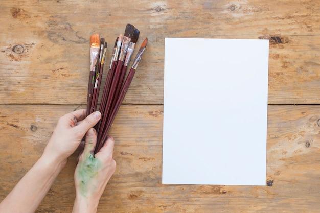 Mains tenant des pinceaux près de papier blanc