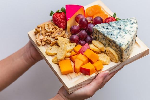 Mains tenant une planche avec divers fromages