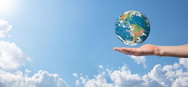 Mains tenant une planète, la terre sur une surface de ciel bleu nature avec de beaux nuages blancs et la lumière du soleil