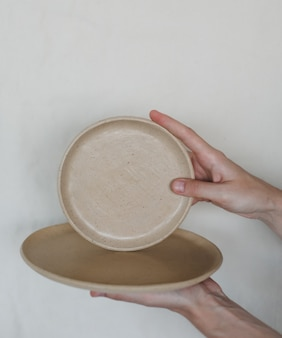Mains tenant des plaques en céramique isolés sur fond blanc. ensemble minimaliste de vaisselle et de poterie en céramique faites à la main