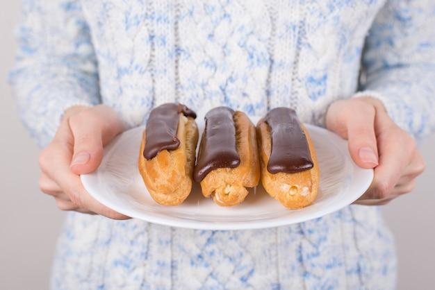 Mains tenant un plat avec trois gâteaux au chocolat glacé