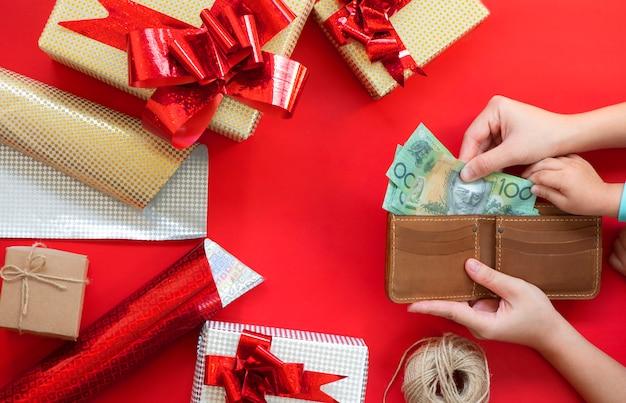 Mains tenant le portefeuille avec de l'argent pour payer des cadeaux