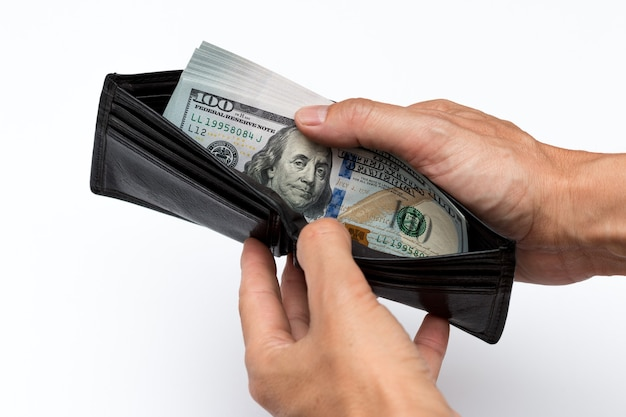 Mains tenant le portefeuille avec des billets de cent dollars isolés sur fond blanc.