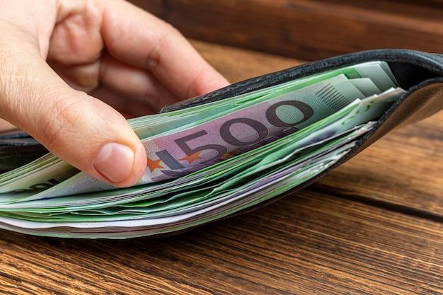 Mains tenant un portefeuille plein de billets d'argent