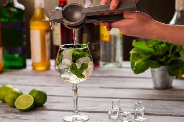 Mains tenant un presse-agrumes. le liquide s'égoutte dans le verre à vin. jus frais pour cocktail hugo. sirop de fleur de sureau et menthe.