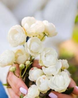 Mains tenant des roses blanches en fleurs