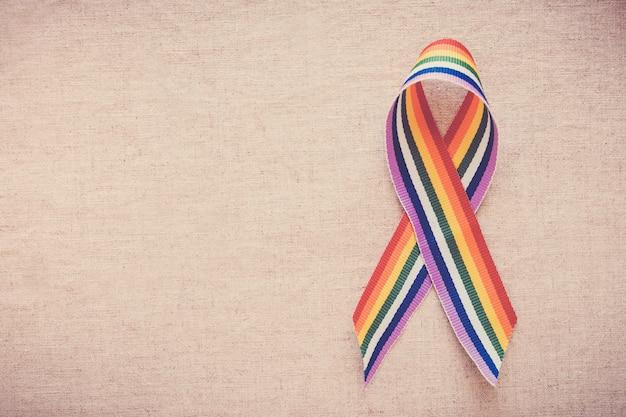 Mains tenant un ruban arc-en-ciel de fierté gay pour la sensibilisation des lgbt