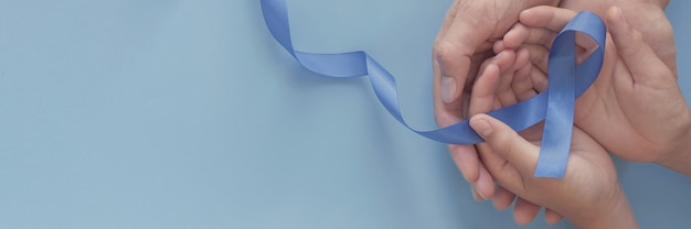 Mains tenant un ruban bleu