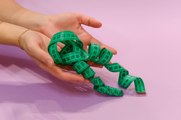 Mains tenant un ruban à mesurer vert sur fond violet