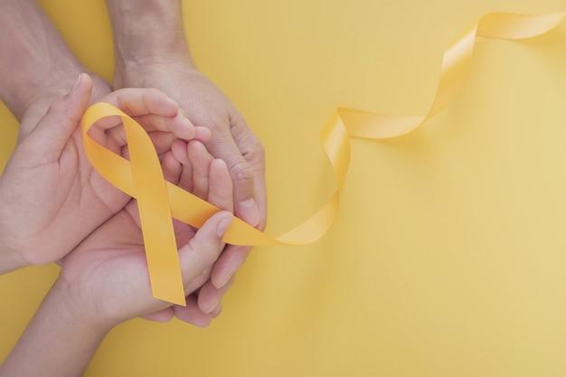 Mains tenant un ruban en or jaune, sensibilisation au sarcome, sensibilisation au cancer infantile, journée mondiale de prévention du suicide