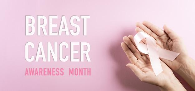 Mains tenant un ruban rose couleur de l'arc symbolique de sensibilisation au cancer du sein