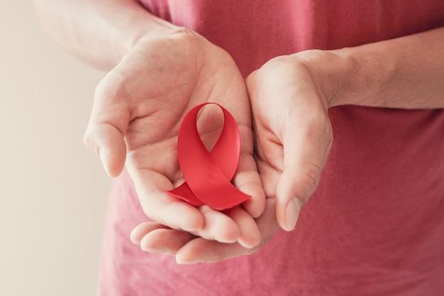 Mains tenant le ruban rouge, concept de sensibilisation au vih, journée mondiale du sida, journée mondiale de l'hypertension