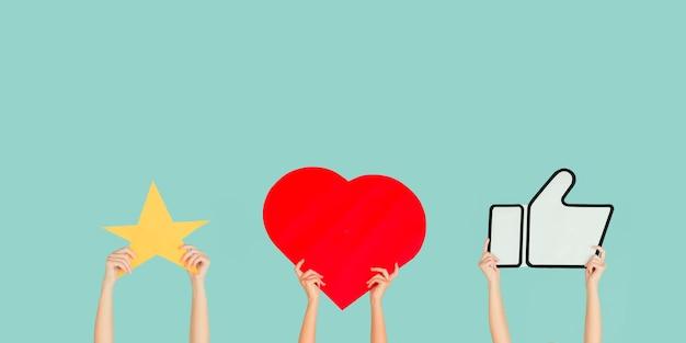 Mains tenant les signes des médias sociaux sur fond bleu studio, flyer. copyspace pour votre texte ou image, publicité. montrer du sens, des gadgets, des technologies modernes, des commentaires, des messages, des interactions.