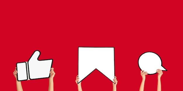 Mains tenant les signes des médias sociaux sur fond de studio rouge, flyer. copyspace pour votre texte ou image, publicité. montrer du sens, des gadgets, des technologies modernes, des commentaires, des messages, des interactions.