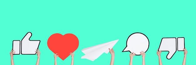 Mains tenant les signes des médias sociaux sur fond turquoise, flyer. copyspace pour votre texte ou image, publicité. montrer du sens, des gadgets, des technologies modernes, des commentaires, des messages, des interactions.