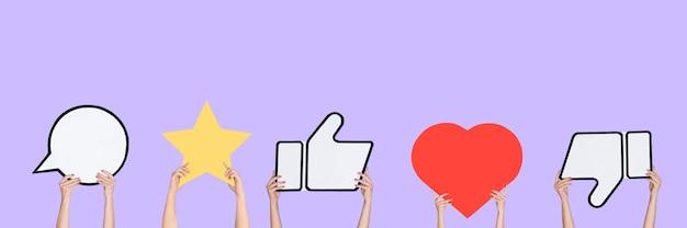Mains tenant les signes des médias sociaux sur fond violet, flyer. copyspace pour votre texte ou image, publicité. montrer du sens, des gadgets, des technologies modernes, des commentaires, des messages, des interactions.