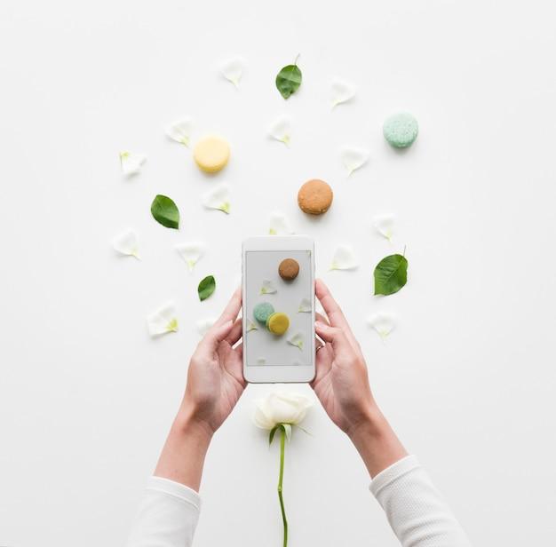 Des mains tenant un smartphone capturent un macaron
