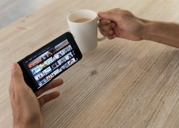 Mains tenant un smartphone montrant l'application vidéo amazon prime