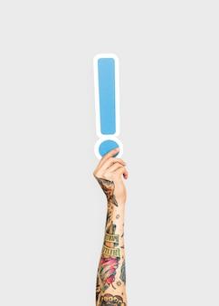 Mains tenant le symbole du point d'exclamation