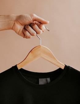 Mains tenant un t-shirt noir dans un cintre