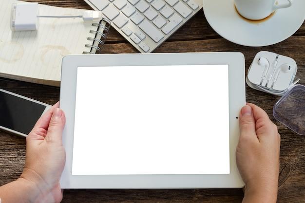 Mains tenant la tablette sur éboulis sur table de travail en bois avec cadre de gadgets