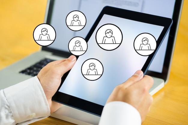 Mains tenant une tablette avec des icônes