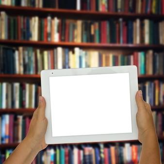 Mains tenant une tablette vide avec des étagères de bibliothèque en arrière-plan