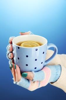 Mains tenant une tasse de boisson chaude, sur fond bleu