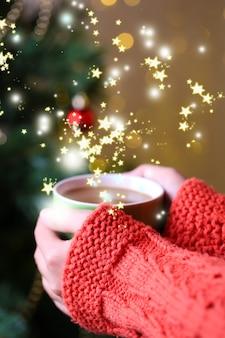 Mains tenant une tasse de boisson chaude, gros plan, sur fond d'arbre de noël