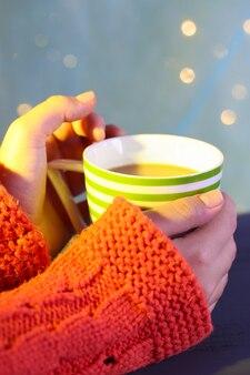 Mains tenant une tasse de boisson chaude, gros plan, sur fond clair