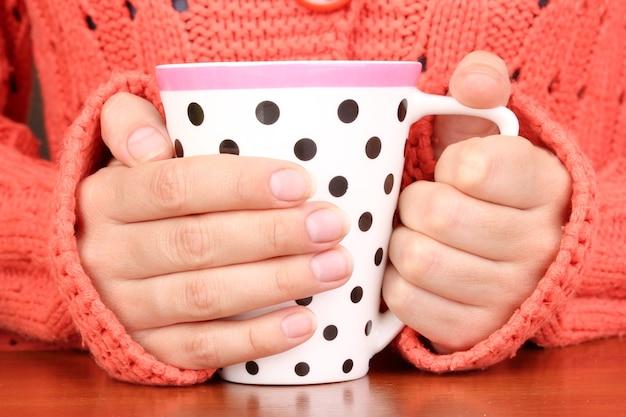 Mains Tenant Une Tasse De Boisson Chaude En Gros Plan Photo Premium