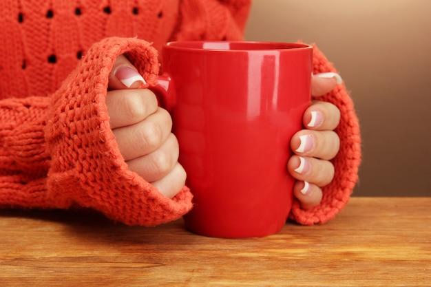 Mains tenant une tasse de boisson chaude, gros plan