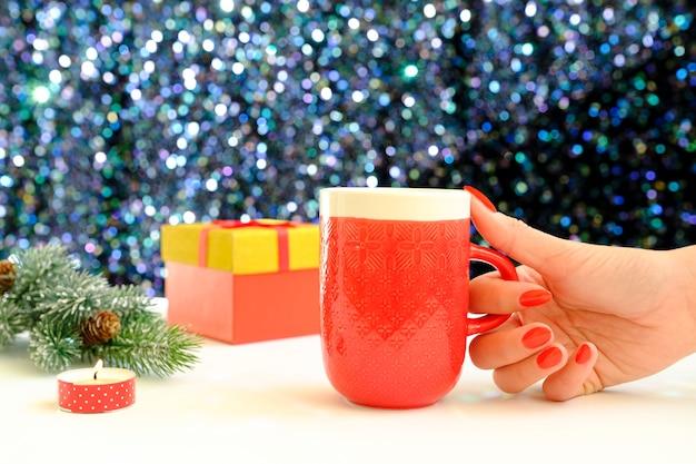 Mains tenant une tasse de café sur un fond de noël. vue d'en-haut. mains féminines tenant une tasse de café. coffrets cadeaux de noël et sapin de neige au-dessus de la table en bois.