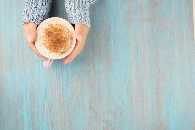 Mains tenant une tasse de chocolat chaud, une table en bois bleue, un pull bleu, une belle manucure rose