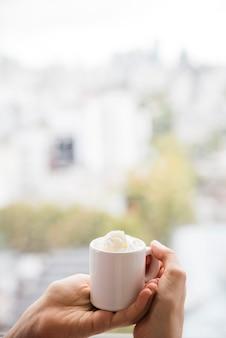 Mains tenant une tasse de thé