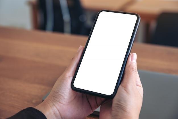 Mains tenant un téléphone mobile noir avec écran blanc vierge avec ordinateur portable sur table en bois