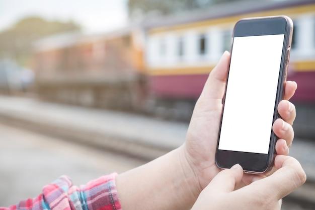Mains tenant et en utilisant un téléphone portable avec écran blanc. former en arrière-plan.