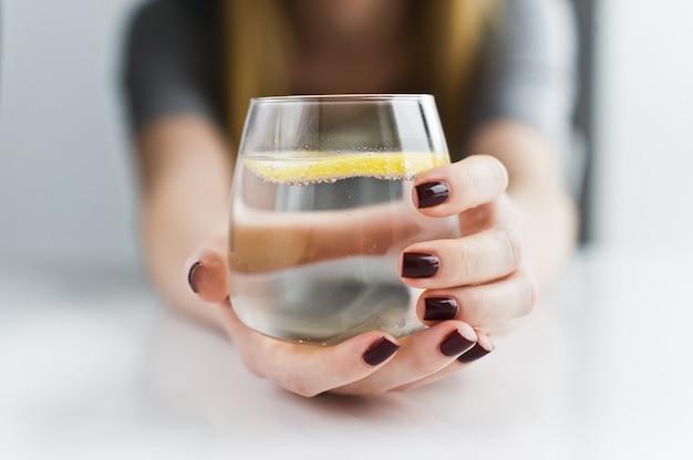 Mains tenant un verre d'eau claire avec du citron.