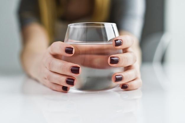 Mains tenant un verre d'eau propre.