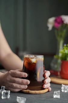 Mains tenant un verre d'espresso avec du jus de citron et des tranches de citron frais