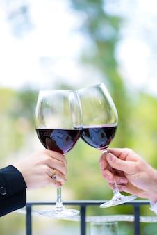Mains tenant des verres à vin rouges à tinter