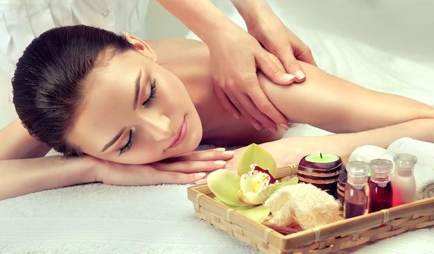Les mains tendres et douces du spécialiste du massage font un massage sur le dos des jeunes
